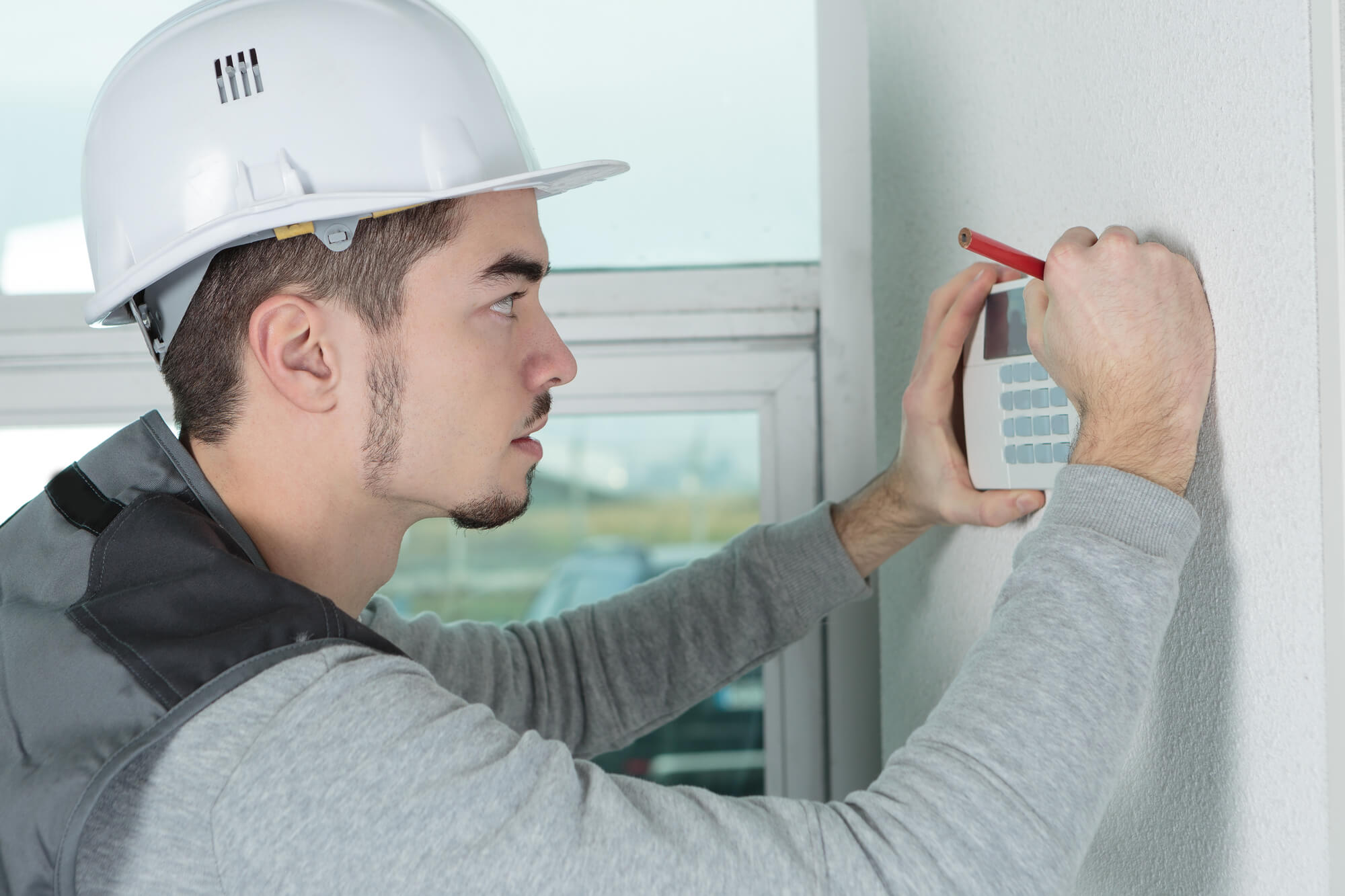 A man installing security systems in a home.